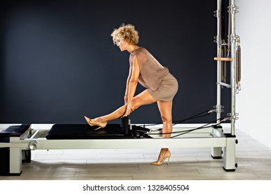 Beautiful middle-aged blonde woman in short evening dress does exercises  in a fitness center.