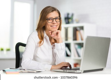 Beautiful middle-aged businesswoman in glasses works in the office