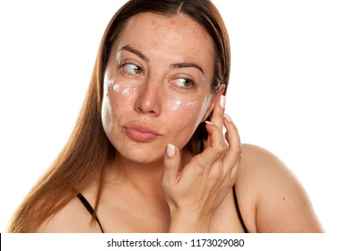 beautiful middle-aged woman applying moisturizer on her face on white background