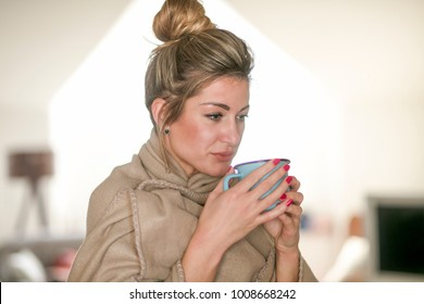Beautiful middle-aged woman drinks tea from a glass in a cold living room dressed in a cotton becouse of cold winter. A sick girl drinks from a blue cup in the living room.