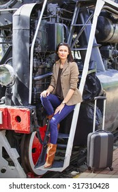 beautiful middle-aged woman going away in the retro-journey on the old steam train