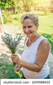 Beautiful middle-aged woman, in her yard in the countryside, arranges flowers of lavender