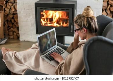 Schöne Frau mittleren Alters neben dem Kamin entspannt sich im Wohnzimmer und arbeitet auf Laptop aus dem Haus. Mädchen in den 30er Jahren befragte für das Projekt Heimwerker