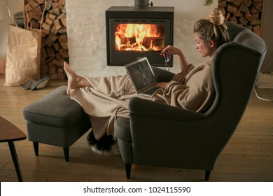 Beautiful middle-aged woman next to the fireplace relaxes in the living room and works on laptop from house. Girl in 30's surveyed for the  home bussiness project