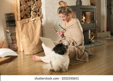 Beautiful middle-aged woman next to the fireplace relaxes in the living room and works on laptop from house. Girl in 30's surveyed for the  home bussiness project with her pet