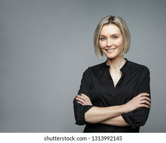Beautiful middle-aged woman on a gray background in a black blouse smiling.