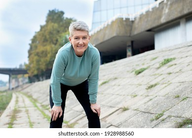Beautiful middle-aged  woman resting after work out outdoor.