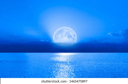 """Beautiful midnight blue sea landscape with a full moon - Moonrise along the coast with dramatic sky """"Elements of this image furnished by NASA"""