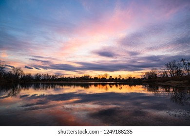 A beautiful Midwest sunset with the clouds turning pink and reflecting onto the calm lake.