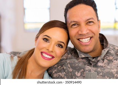 beautiful military couple sitting on sofa at home