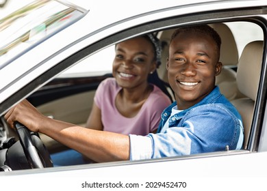 Beautiful millennial afro american couple posing in their new auto, cheerfully smiling at camera while making test drive, side view, closeup. Happy black man and woman going summer vacation by car