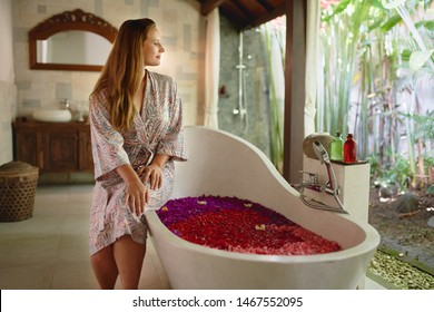 Beautiful millennial woman relaxing outside large bathtub filled with flower petals in tropical spa setting