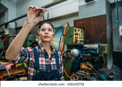 beautiful milling machine female staff wearing safety goggles focus on components finished product standing in front of technology machine.