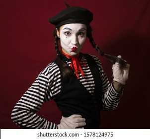Beautiful mime girl smiles and holds her pigtails with her hands.
