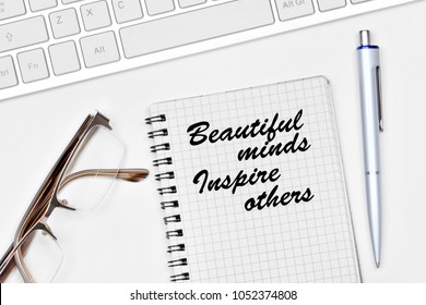 Beautiful minds inspire others. Text on notebook on a white background close-up