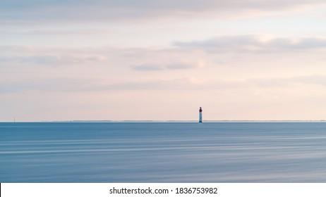 Beautiful minimalist seascape at sunset with Chauveau lighthouse. Rivedoux, Re Island, France