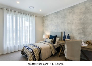 Beautiful and minimalist shades of off-white and grey with a hint of blue livens up the bed set and the desk with a single high- sofa.