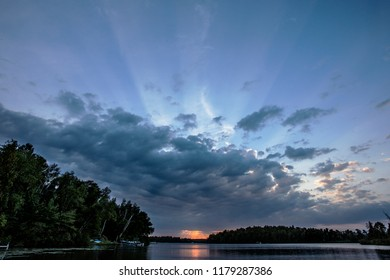 Beautiful Minnesota north woods lake bay at the end of a gorgeous sunset with fingers of light streaking out of the clouds