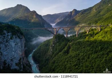 Beautiful misty morning view of Djurdjevica bridge over the river Tara in Montenegro, Europe. Beautiful world of Mediterranean countries. Aerial panorama.