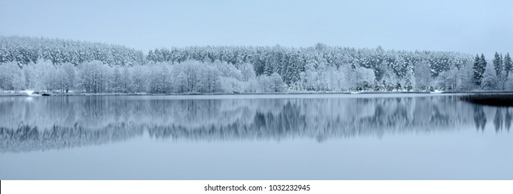 Beautiful misty winter panorama. Scenic landscape .Snowy forest by the lake in Lithuania