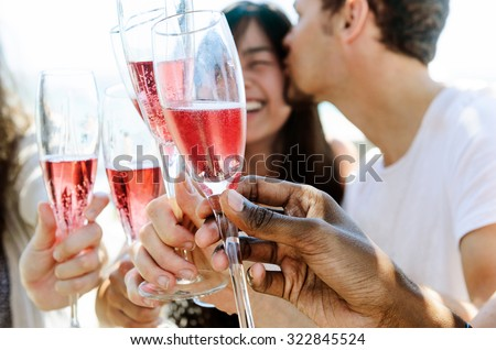 Beautiful mix race couple celebrating their engagement with champagne and their friends on the beach