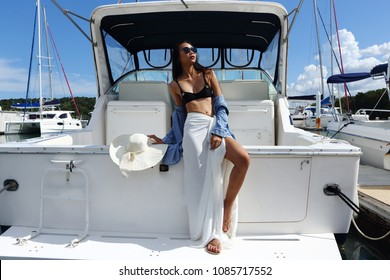 Beautiful Mix Race Tanned skin Woman walk along Luxury Yachts in Marina, Black bikini Big Hat Jean Shirt Girl post as Fashion Model in docking pier under summer blue sky in vacation holiday