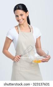 Beautiful mix race woman wearing an apron beating eggs