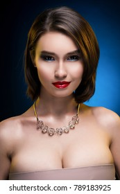 Beautiful mixed asian-caucasian race girl wearing necklace. Advertising and Commercial Design. Shopping. Jewelry - Earrings. Big Breast. Blue-black background. Red lips. Healthy clean skin.