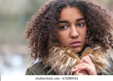 Beautiful mixed race African American girl teenager female young woman outside wearing fake fur collar coat looking sad depressed or thoughtful