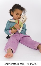 A beautiful mixed race girl playing with her favorite doll