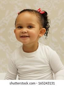 Beautiful mixed race toddler posing in studio setting, happy smiling face.