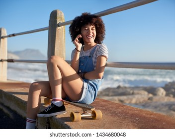 Beautiful mixed race woman with afro talking on mobile phone cellphone outdoors, relaxed happy smiling
