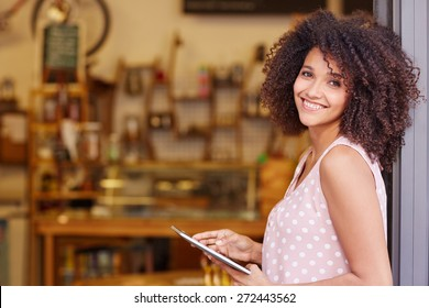 Beautiful mixed race woman with an afro hairstyle holding a digital tablet while standing in the doorway of her coffee shop