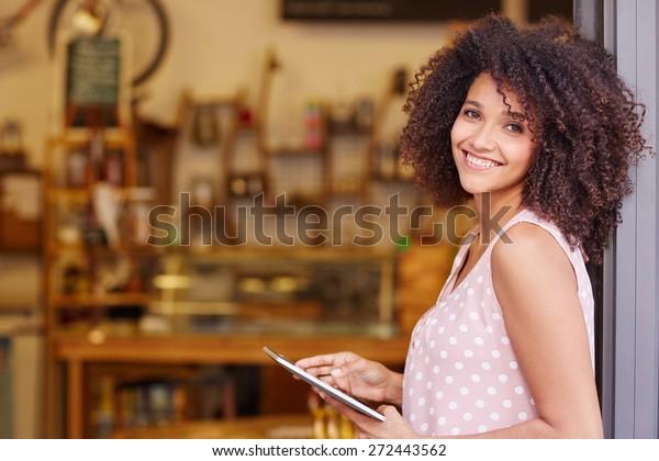 Schöne gemischte Rasse-Frau mit einer afro-Frisur, die eine digitale Tablette hält, während sie in der Tür ihres Cafés steht