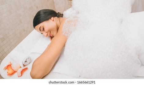 Beautiful mixed race woman enjoying warm foam in hammam. Body recovery at hamam, turkish bath