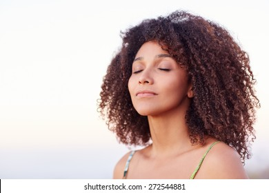 Beautiful mixed race woman with her eyes closed outdoors in a serene moment
