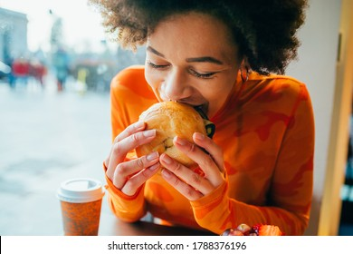 Beautiful mixed race woman indoors eating burger - Multiethnic female enjoying meal in fast food - eating, delicious, cheerful concept