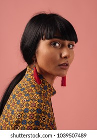 Beautiful mixed race woman with long black hair. Creative portrait of a fashion model posing at studio on rose pink backbround.