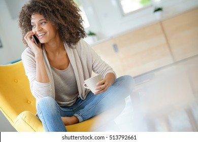 Beautiful mixed race woman talking on phone at home