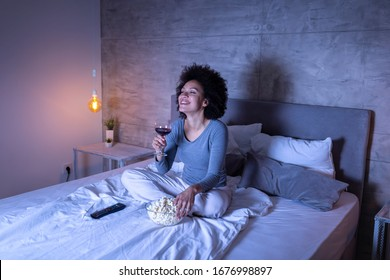 Beautiful mixed race woman wearing pajamas sitting on bed, eating popcorn, drinking wine and watching a comedy movie on TV, relaxing at home at night