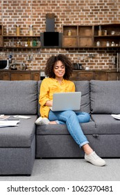 beautiful mixed race woman working working with laptop on couch