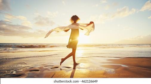 Schöne gemischte Rasse junge Frau, die bei Sonnenuntergang am Strand spaziert