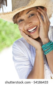 A beautiful mixed race young woman laughing and having fun wearing a straw cowboy hat, shot under a palm tree on a tropical beach