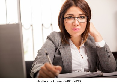 Beautiful mixed-race business woman working and taking notes at work and making eye contact