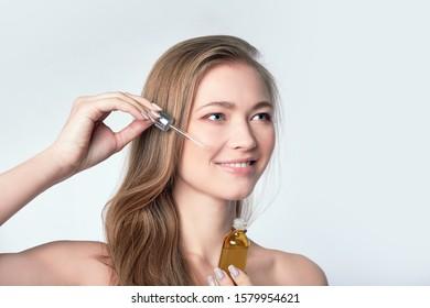 beautiful model applying a skin serum treatment on white. Spa, skincare and wellness. Close up, copyspace - Shutterstock ID 1579954621