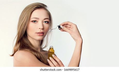 beautiful model applying a skin serum treatment on white. Spa, skincare and wellness. Close up, copyspace - Shutterstock ID 1669895617