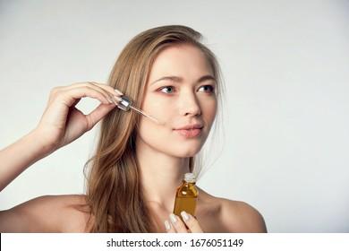 beautiful model applying a skin serum treatment on white. Spa, skincare and wellness. Close up, copyspace - Shutterstock ID 1676051149