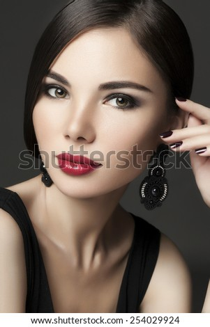Beautiful model of Asian appearance with evening make-up and elegant hairstyle on dark background. Red lips. Smoky eyes. - Image