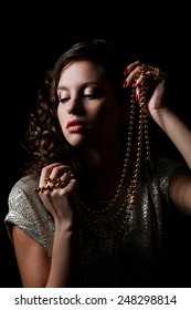 Beautiful model with beads in hands on dark background