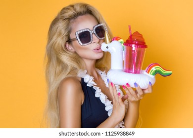 Beautiful model in a bikini and sunglasses, holding a drink and an inflatable unicorn.